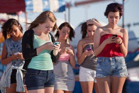 Young women using smartphones at an amusement park